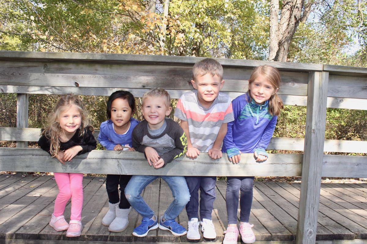Kids peek through the bridge railing