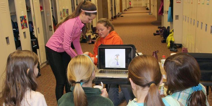 8th Graders use laptop to present their faith stories to younger buddies