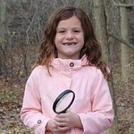 girl with magnifying glass -outdoors